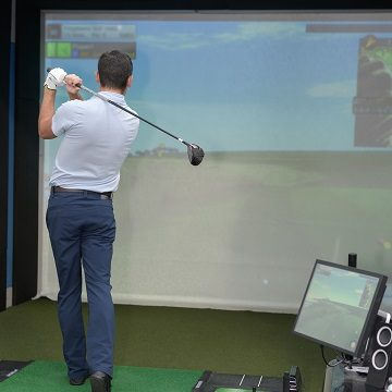 Man practicing golf on indoor simulator